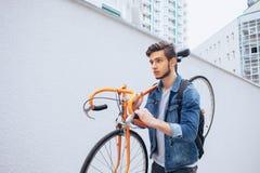 蓝色牛仔裤夹克的人继续他的肩膀桔子自行车 橙色固定自行车的一个年轻人 免版税库存图片