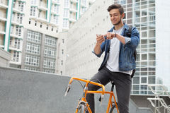 蓝色牛仔裤夹克的人继续他的肩膀桔子自行车 免版税库存照片