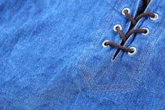 蓝色牛仔裤构造与被栓的绳索 免版税库存照片