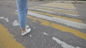 蓝色牛仔裤的一个女孩横渡一条行人交叉路 影视素材