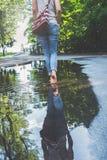 蓝色牛仔裤的赤足妇女走通过水水坑的在城市布局的 库存图片