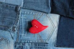 蓝色牛仔裤详述和红色心脏蜡烛 免版税库存图片