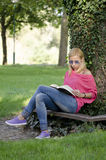 蓝色牛仔裤阅读书的少妇 免版税库存照片