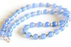 蓝色玉髓成串珠状与银色间隔号的项链 免版税库存照片