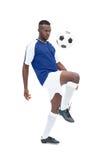 蓝色球衣控制球的足球运动员 免版税图库摄影