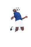 蓝色球衣控制球的足球运动员 免版税库存图片