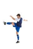 蓝色球衣踢的足球运动员 库存照片