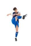 蓝色球衣踢的足球运动员 免版税库存照片