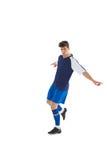 蓝色球衣踢的足球运动员 免版税图库摄影