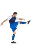 蓝色球衣踢的足球运动员 图库摄影