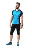 蓝色球衣T恤杉和绑腿的年轻有胡子的骑自行车者人放松了微笑和看  图库摄影