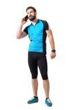 蓝色球衣T恤杉的年轻有胡子的适合骑自行车者在查寻的电话 库存照片