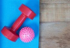 蓝色瑜伽席子和红色哑铃 免版税图库摄影
