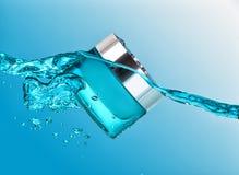 蓝色瓶子在大海波浪的润湿的奶油与大气泡 图库摄影
