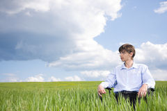 蓝色生意人草原坐的天空下 免版税库存图片