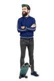 蓝色田径服夹克和棒球帽的年轻行家在看的滑板微笑 库存照片