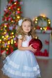 蓝色白色典雅的晚礼服的年轻美丽的女孩坐地板在圣诞树附近和礼物在一个新年 免版税库存照片