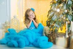 蓝色白色典雅的晚礼服的年轻美丽的女孩坐地板在圣诞树附近和礼物在一个新年 免版税库存图片
