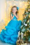 蓝色白色典雅的晚礼服的年轻美丽的女孩坐地板在圣诞树附近和礼物在一个新年 图库摄影