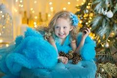 蓝色白色典雅的晚礼服的年轻美丽的女孩坐地板在圣诞树附近和礼物在一个新年 库存照片