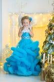 蓝色白色典雅的晚礼服的年轻美丽的女孩坐地板在圣诞树附近和礼物在一个新年 库存图片