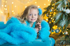 蓝色白色典雅的晚礼服的年轻美丽的女孩坐地板在圣诞树附近和礼物在一个新年 免版税图库摄影