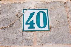 蓝色白色葡萄酒房子号码四十40在老年迈的墙壁上 库存图片