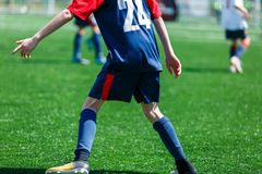 蓝色白色运动服奔跑的,一滴,对橄榄球场的攻击男孩 有球的年轻足球运动员在绿草 ?? 免版税库存照片