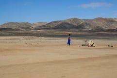 蓝色的妇女在与山的一个沙漠风景在纳米比亚 免版税库存照片