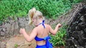 蓝色的小白肤金发的女孩在道路跳跃反对绿色植物 股票视频