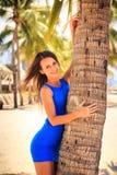 蓝色的深色的女孩赤足接触棕榈反对棕榈行 免版税库存照片