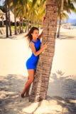 蓝色的深色的女孩赤足接触棕榈反对棕榈行 库存照片