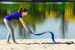 蓝色的年轻浅黑肤色的男人炫耀T恤杉健身锻炼的stellite席子在海滩 图库摄影