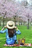 蓝色皮夹克的美丽的年轻白种人妇女有野餐用草莓新月形面包橙汁葡萄在日本樱桃 图库摄影