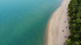 蓝色盐水湖和沙滩与棕榈 蓝色盐水湖和太阳床鸟瞰图在沙滩的与可可椰子和 股票录像