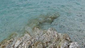 蓝色盐水湖海滩海岸, Kassiopi村庄,科孚岛海岛,希腊 爱奥尼亚海岩石海岸用清楚的绿松石水 股票视频