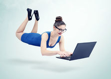 蓝色盘旋在与膝上型计算机的天空中的礼服和玻璃的少妇 图库摄影