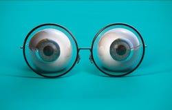 蓝色眼珠和圆的玻璃 库存图片