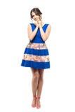 蓝色短的礼服的逗人喜爱的迷人的女性妇女微笑与在手上的头的 免版税图库摄影
