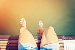 蓝色短裤的人坐 免版税图库摄影