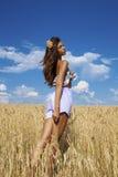 蓝色短裤的性感的少妇在麦子金黄领域 图库摄影