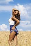 蓝色短裤的性感的少妇在麦子金黄领域 免版税库存图片