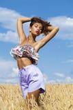 蓝色短裤的性感的少妇在麦子金黄领域 免版税库存照片