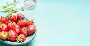 蓝色碗用在绿松石破旧的别致的背景的庭院有机草莓 免版税库存图片