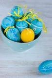 在碗的蓝色和黄色复活节彩蛋 免版税库存照片
