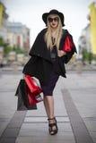 蓝色礼服、外套、太阳镜和帽子的美丽的年轻时髦的白肤金发的妇女有购物袋的走在城市的 免版税库存照片