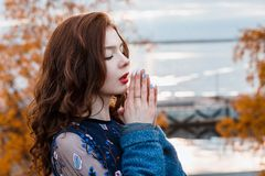 蓝色礼服和外套的特写镜头画象美丽的卷曲女孩在秋天公园温暖她的手呼吸 免版税图库摄影