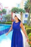 蓝色礼服和白色帽子的妇女微笑由游泳池的 免版税库存照片