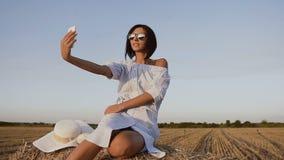 蓝色礼服和sunglassesenjoying的自然的可爱的少妇在干草堆在电话做一张照片,  股票录像