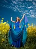 蓝色礼服摆在的美丽的少妇室外与多云剧烈的天空在背景中 图库摄影